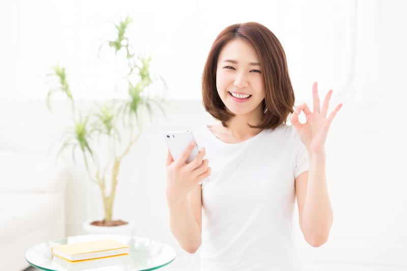 スマホを使う笑顔の女性